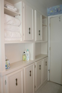 Dingy cupboards with outdated hardware.